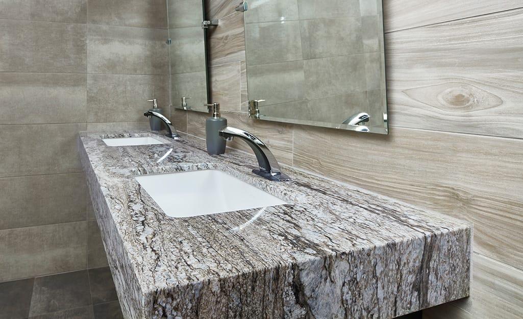 Thick natural stone granite countertop in a bathroom.