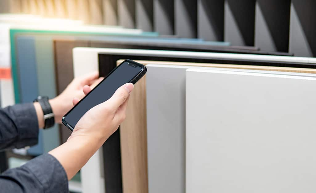 Person holds smartphone while comparing different slabs of quartz countertops.