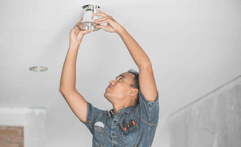 A person installing a recessed light in the ceiling.