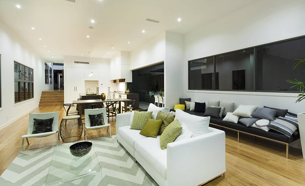 An open concept living room with three rows of ceiling recessed lighting.
