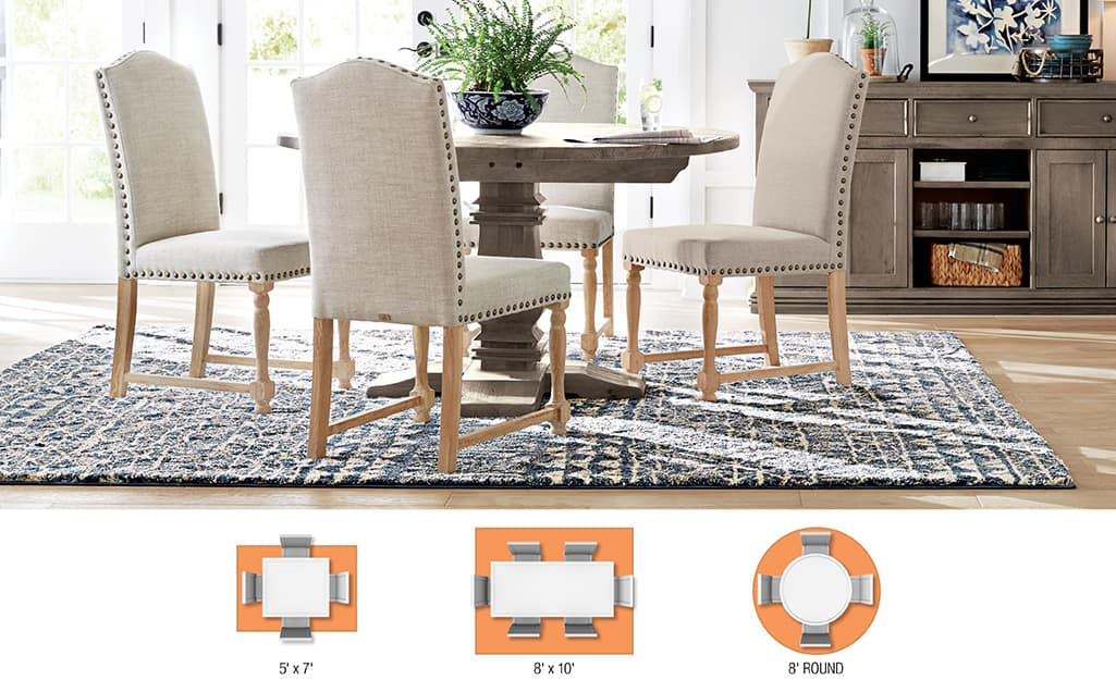 A dining table and four chairs framed by an area rug.