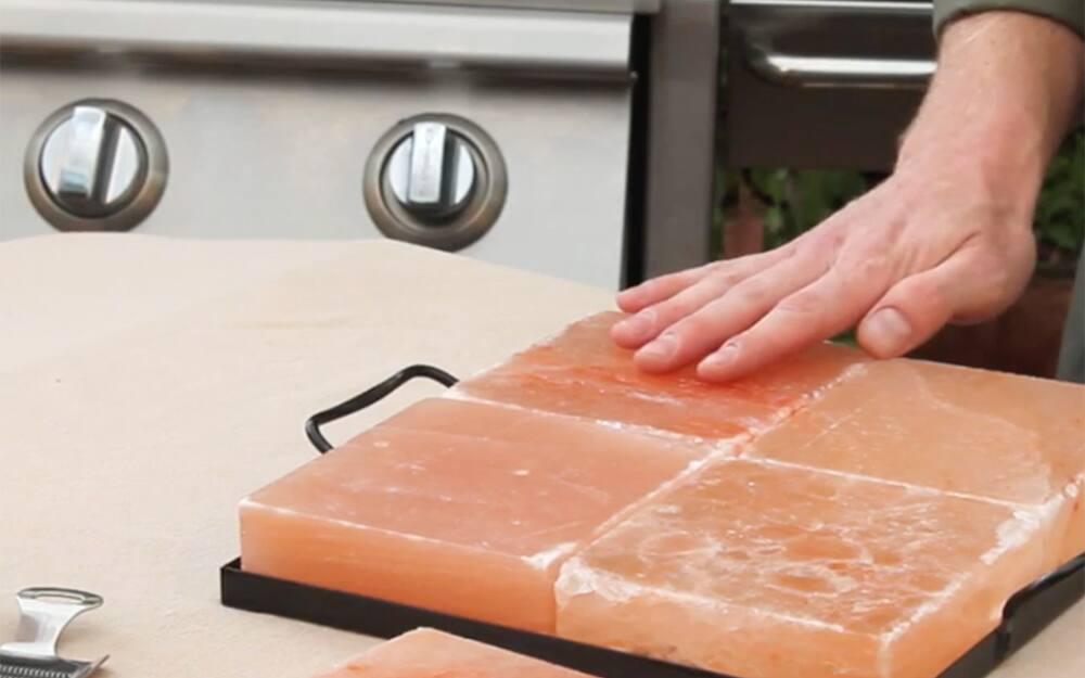 A hand on the surface of a salt slab.