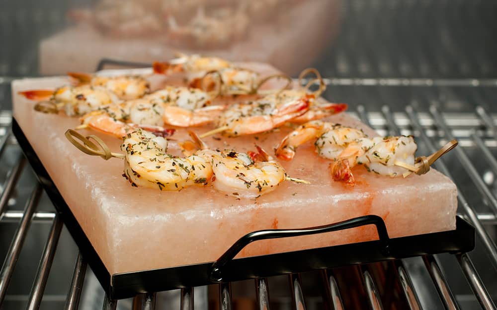 A salt slab with food on top in a oven.