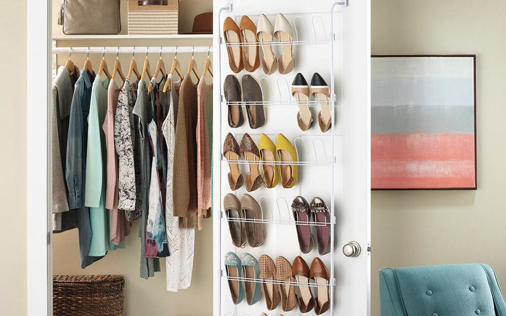 A closet with a hanging shoe rack filled with shoes