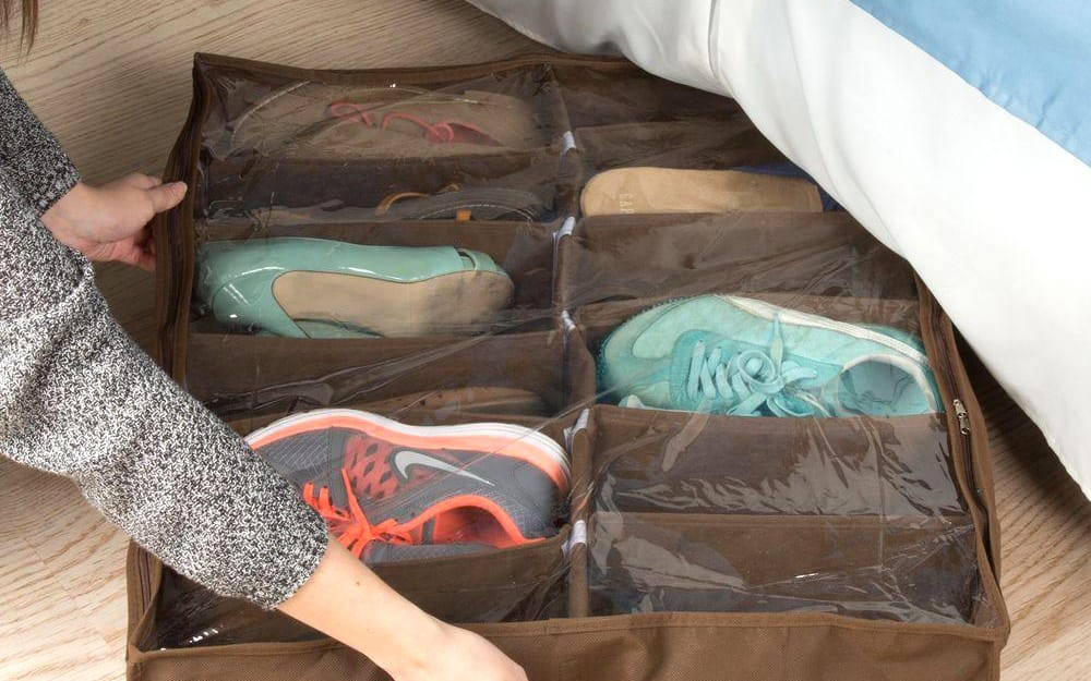 A woman pushing an organizer filled with shoes under the bed