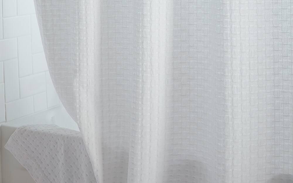 A neutral white shower curtain hanging over a bathtub