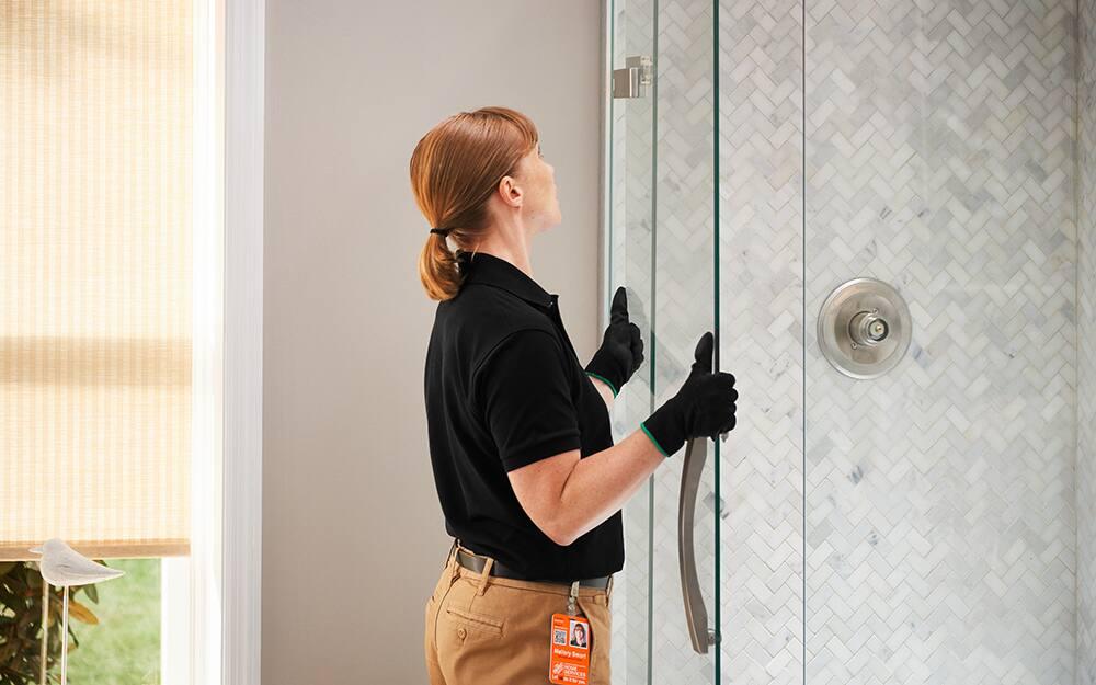A person installing a glass shower door.