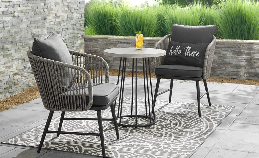 a small patio featuring a wooden 3 piece bistro set