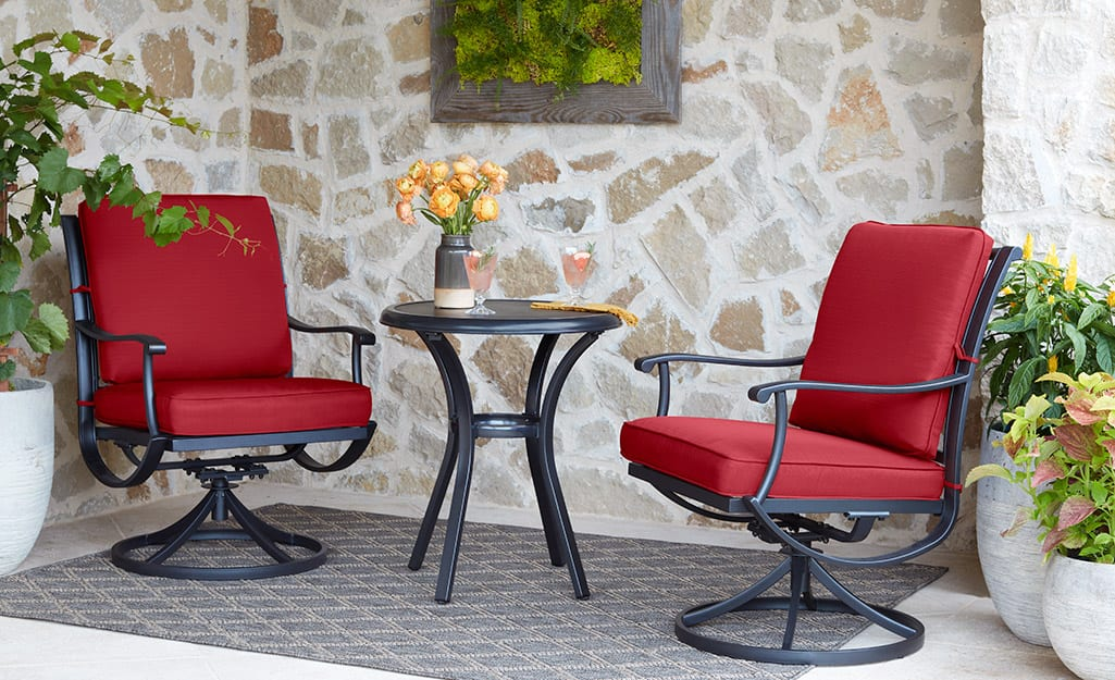 Two chairs and a side table in front of a mirror hanging on the wall of a small patio.