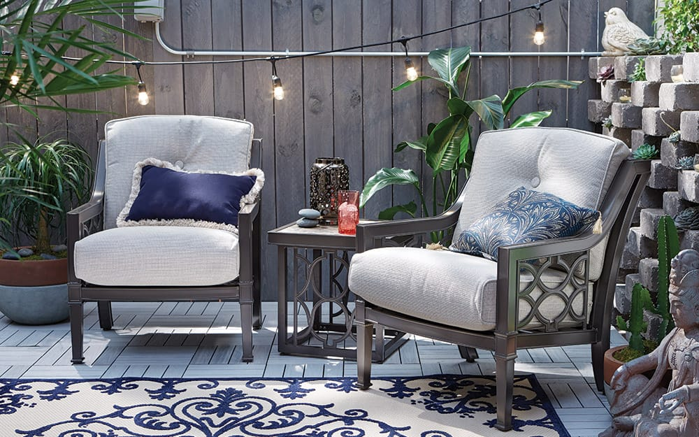 A small patio with outdoor plants and string lights.