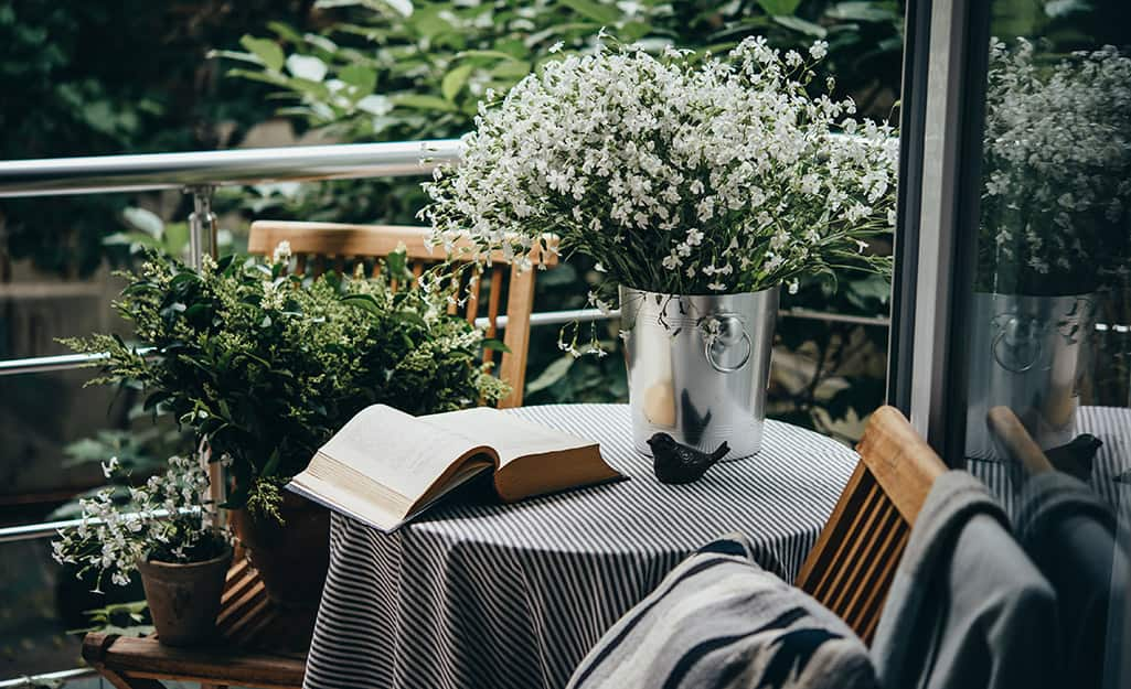 A book and a vase with flowers sitting on a small round table on a patio.