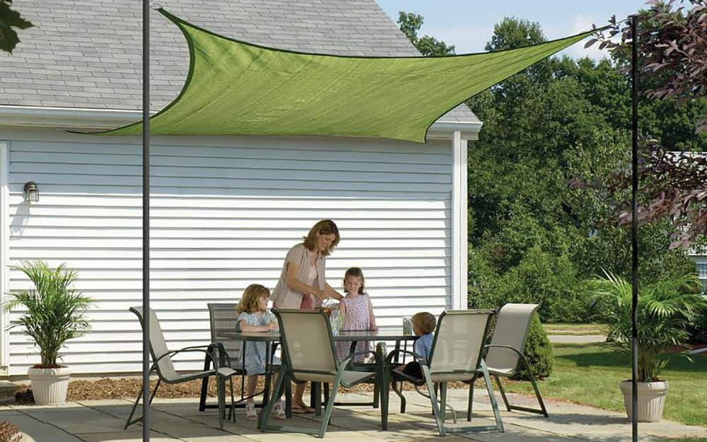 a family gathered around a patio dining set covered by a sun sail