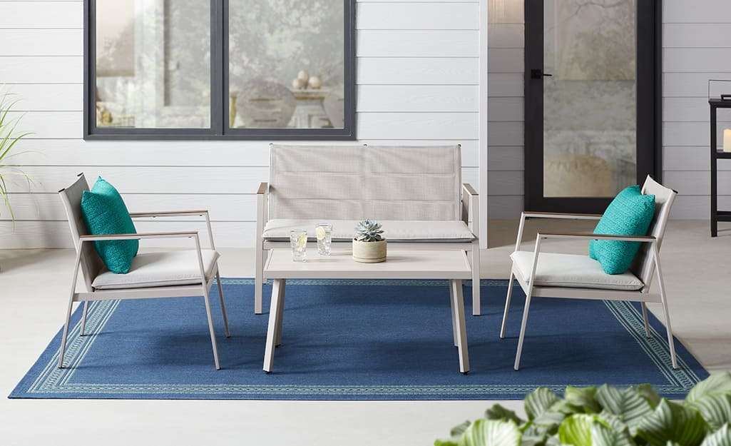 Two metal chairs and a side table on a small. brick patio.
