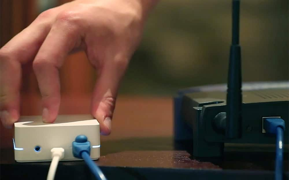 A person connecting a smart home device to a router.