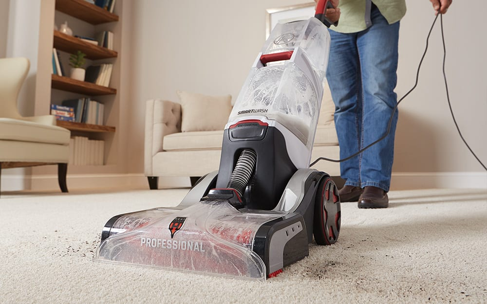 A person using a carpet cleaner to clean a carpet