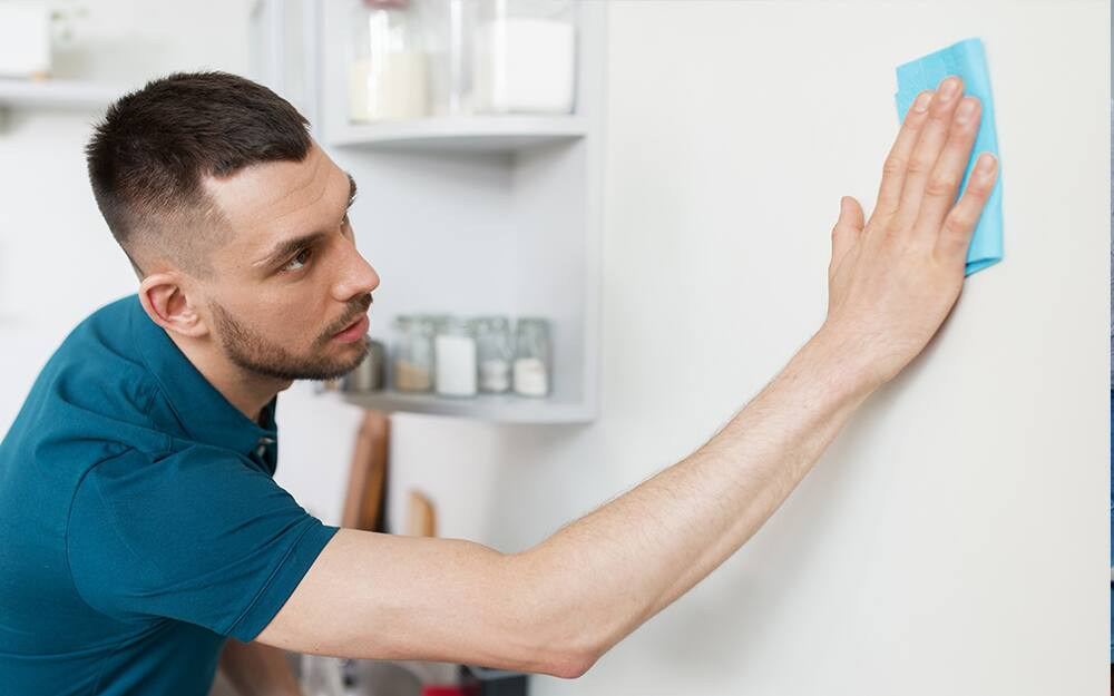 Man cleaning walls with a sponge