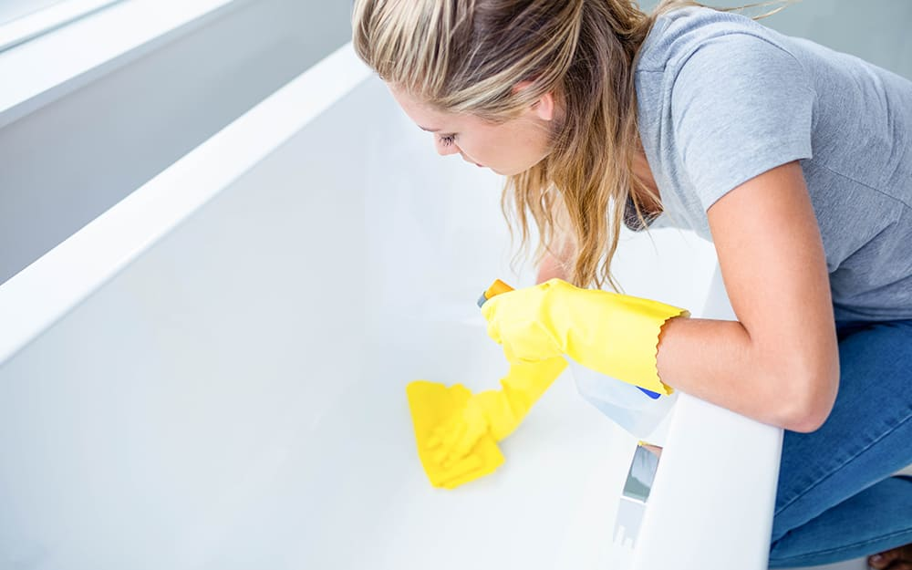 Woman wearing rubber gloves and cleaning a bathtub