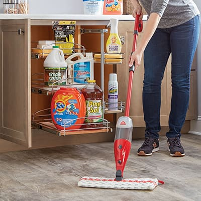 Someone mopping a floor beside an open cabinet filled with cleaning supplies
