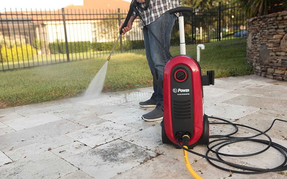 Someone using a pressure cleaner to clean a patio.