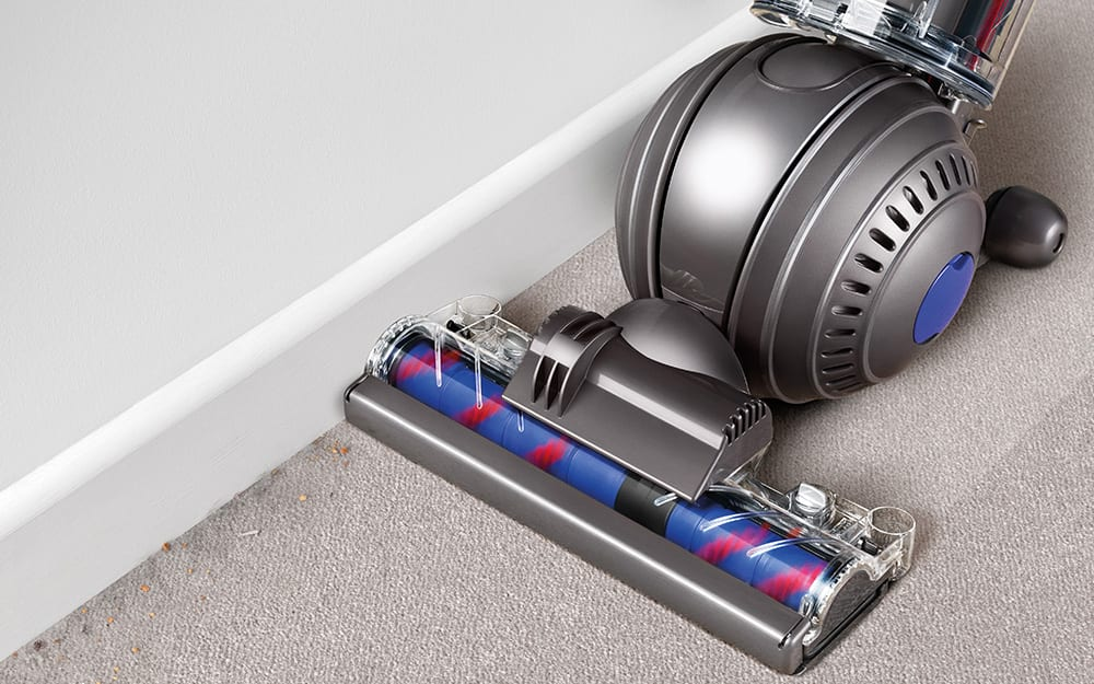 Vacuum cleaner being used along baseboard.