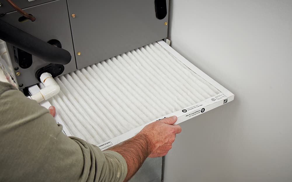 Person changing an air filter.