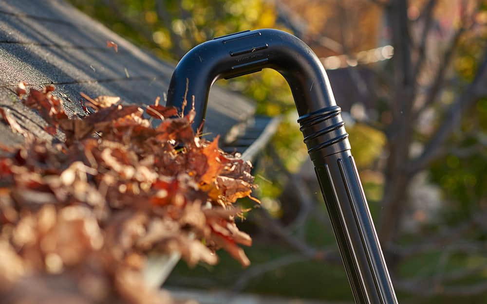 Using a gutter cleaner to remove leaves from a roof gutter.
