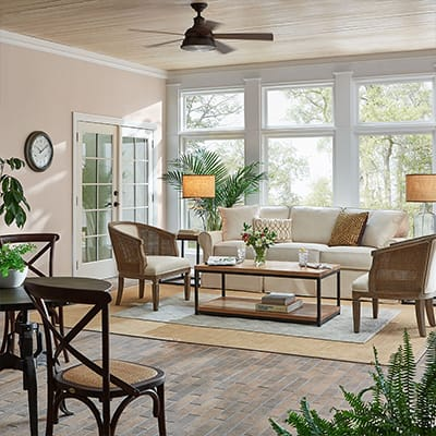 A sunroom with large windows, chairs, a sofa, area rugs and a ceiling fan.