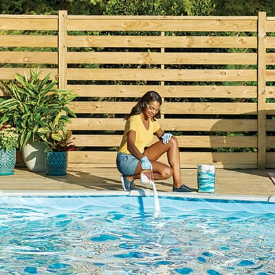 A woman wearing safety glasses and gloves adds pool shock to her swimming pool.