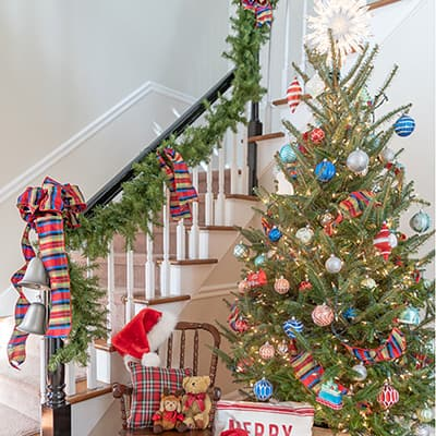 A home decorated for Christmas with garland, bows, and a Christmas tree.
