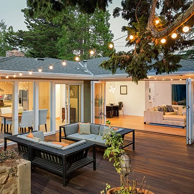 A spacious deck made of wood complete with lighting and patio furniture.