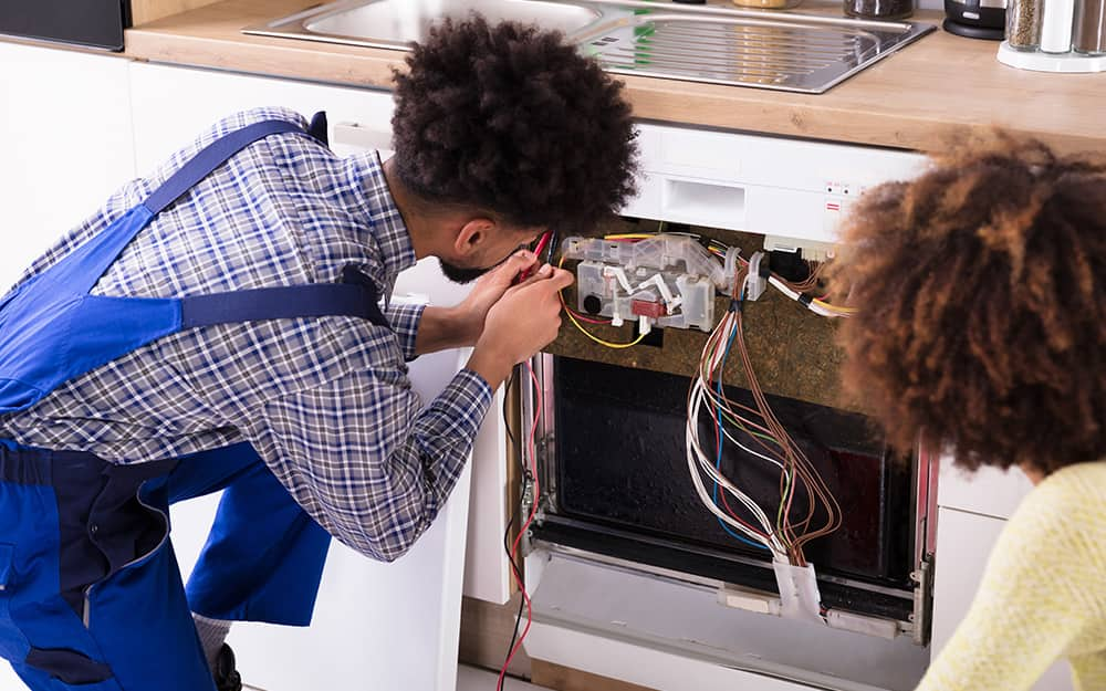 Two people look at the electrical components of a dishwasher.