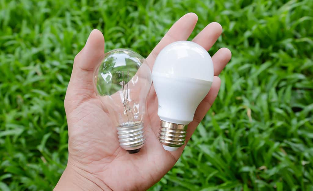 A person holding an incandescent light bulb on the left and an LED light bulb on the right.