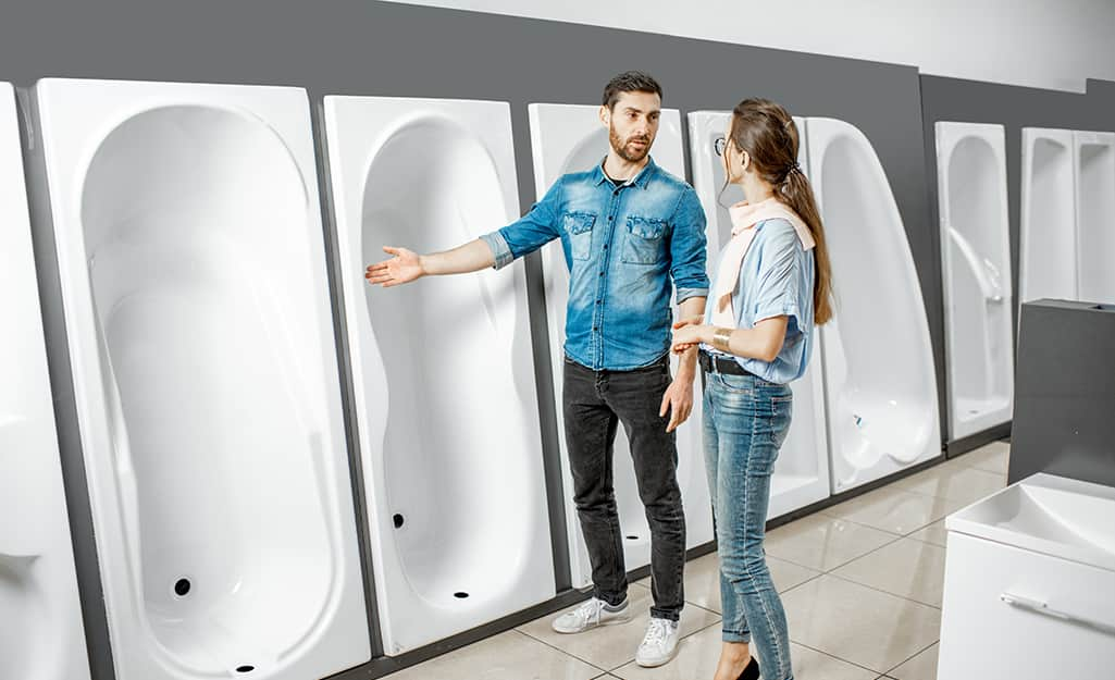 A man and a woman shop for a type of bathtub from a showroom selection of bathtub shapes.