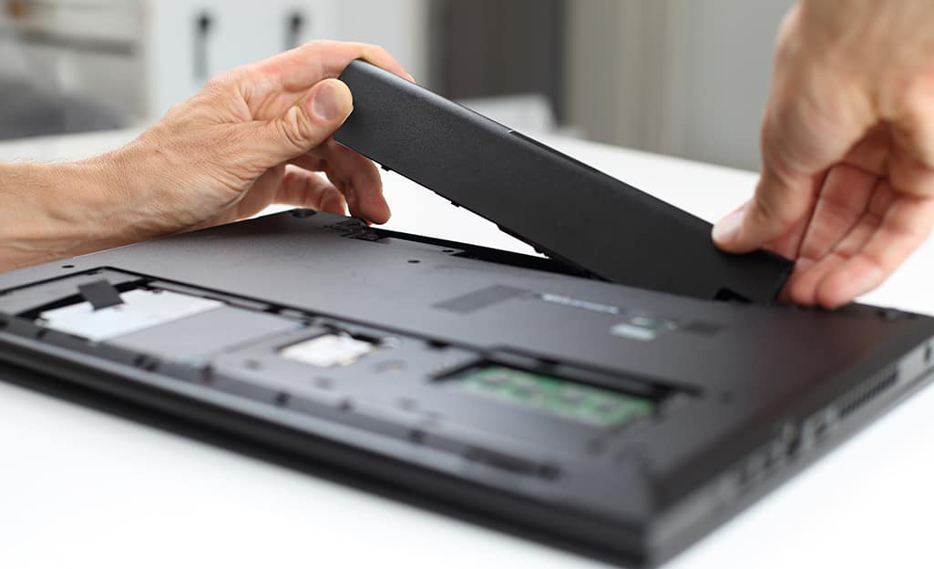 A person inserts a battery into a laptop computer.