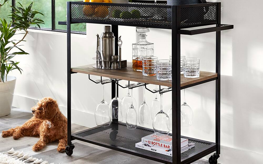 An ice bucket and a potted plant sit on a bar cart with a built-in stemware rack.