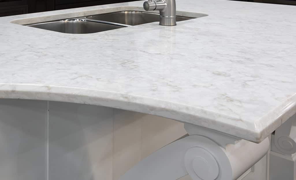A white granite countertop with beveled edges.