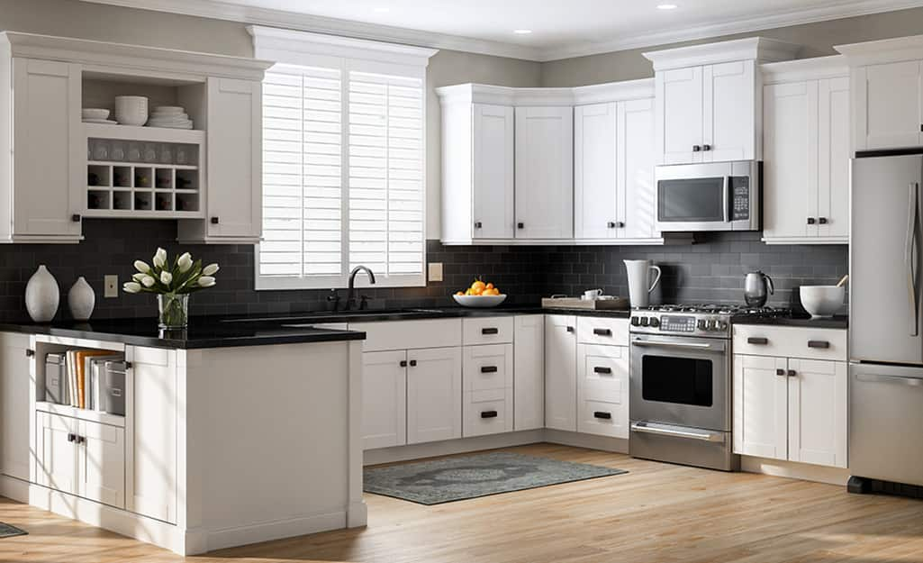 A kitchen with white cabinets and black countertops.