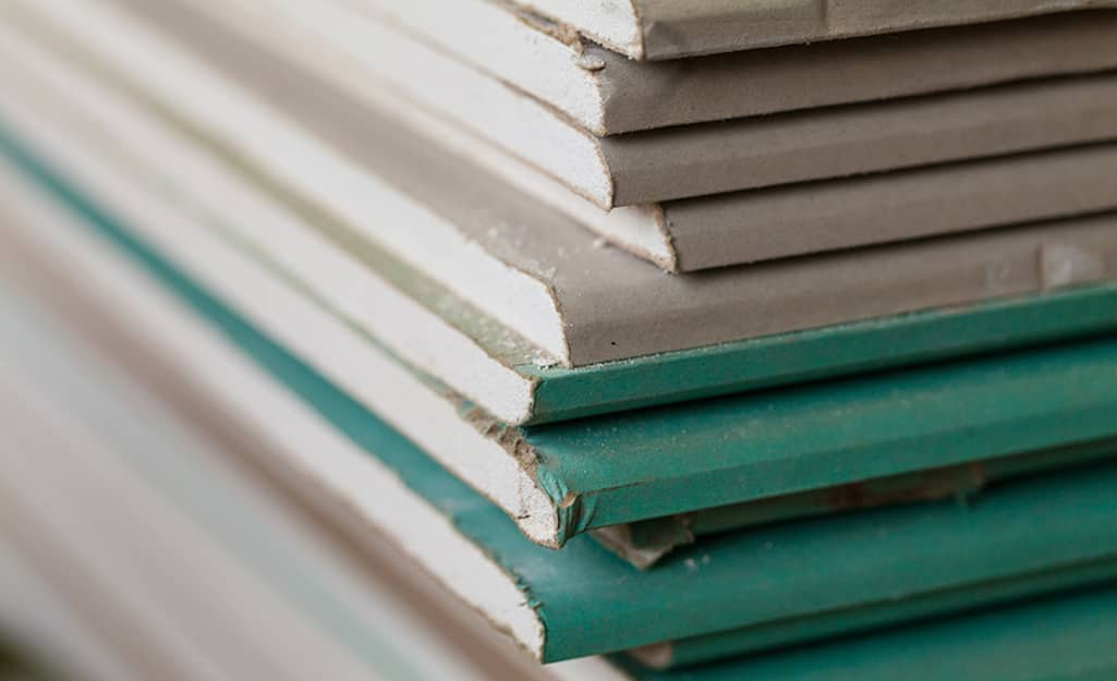 Stacks of drywall sheets in different shades.