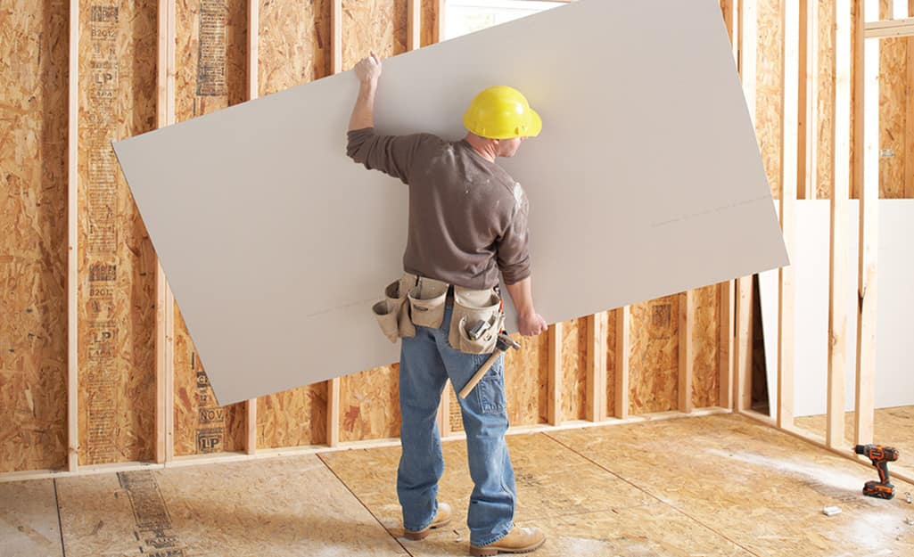 A man holding a large sheet of drywall in an unfinished space.