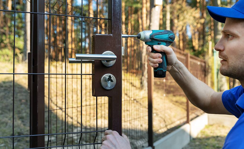 A person installing a gate on a fence.