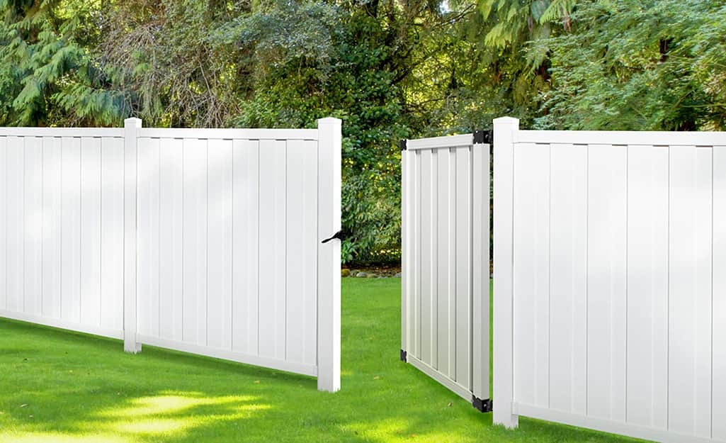 A white vinyl fence with an open gate.