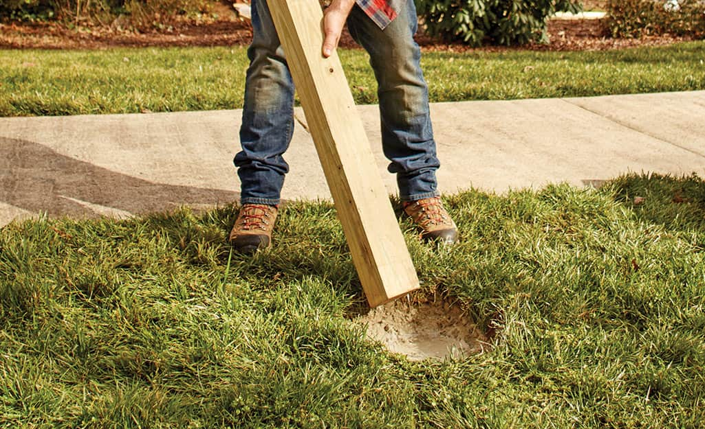 A person installing a fence post in a post hole filled with cement.