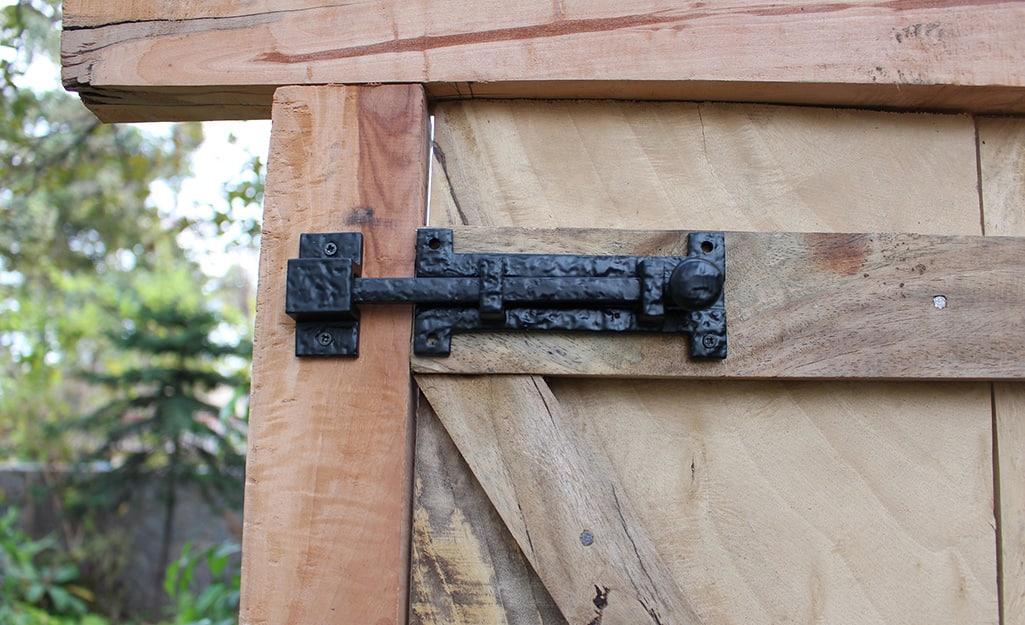 Close image of a iron bolt latch on a wood gate