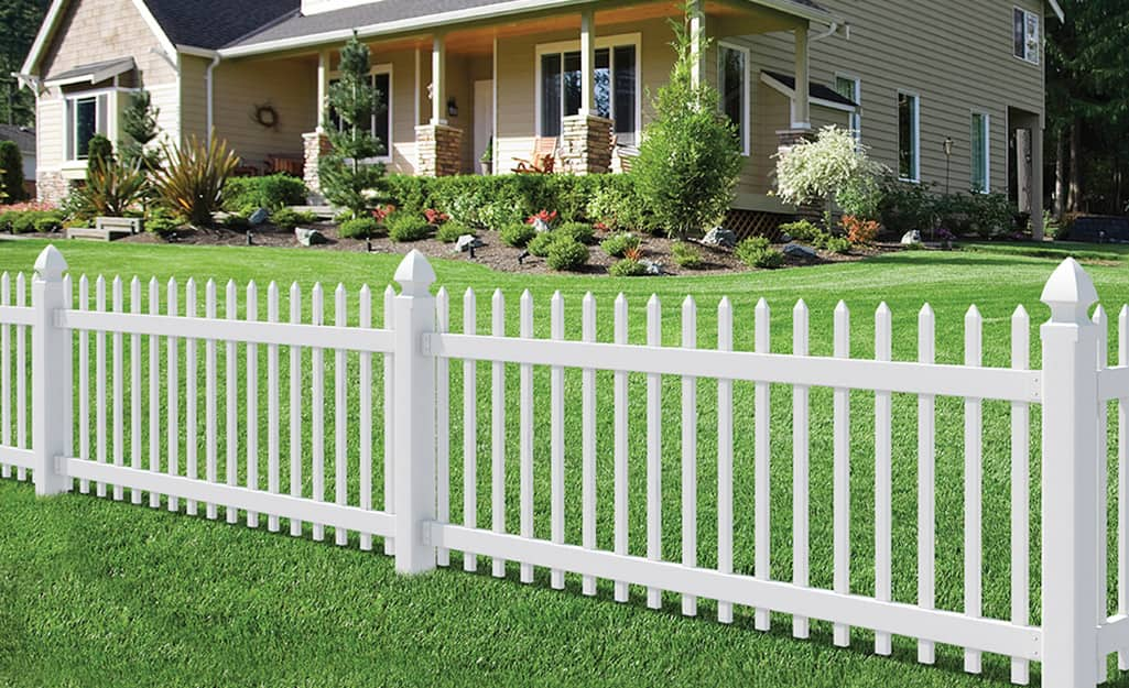 White vinyl fencing along a green yard.