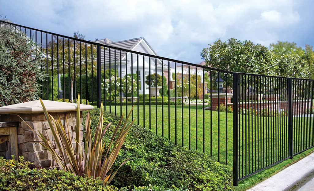 Black metal fence surrounding a large property.