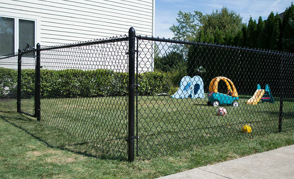 A black chain link fence around a small yard.