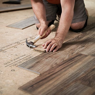 A person installing flooring over a plywood subfloor.
