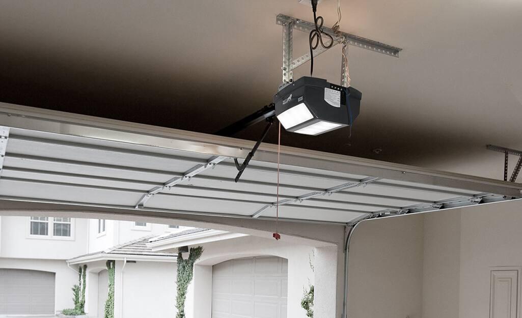 A belt drive garage door opener hangs from a ceiling.
