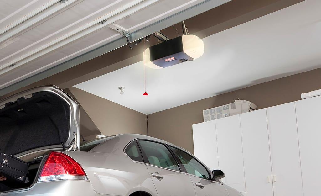 A chain drive garage door opener hangs from a ceiling.