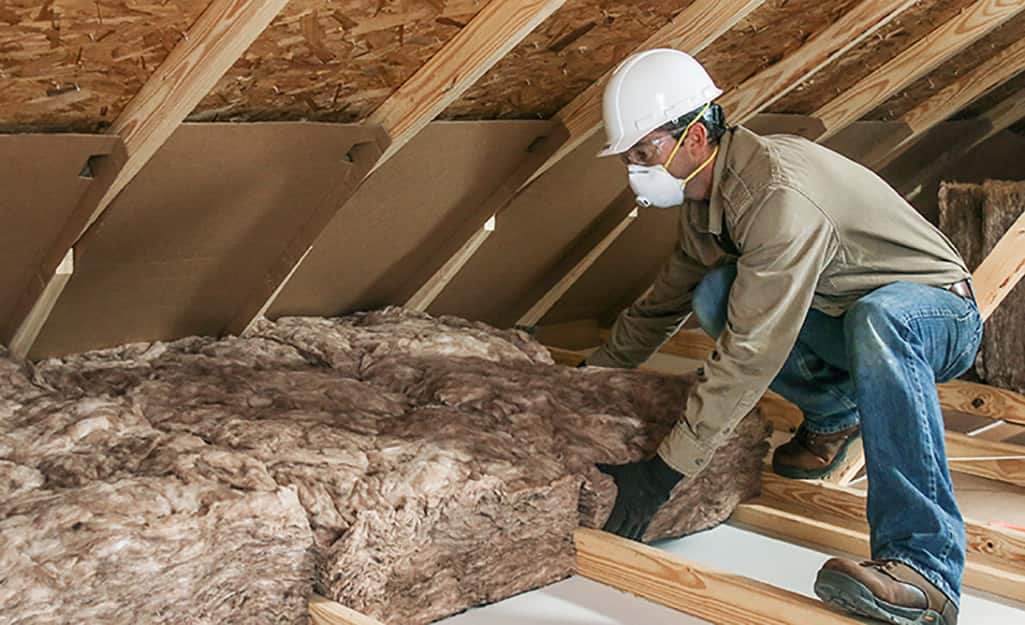 A person putting in insulation in an attic.